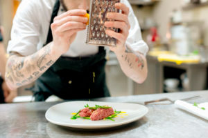 Chef preparing raw meat dish in kitchen