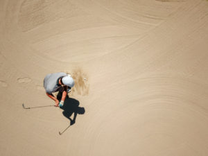Man playing golf on bunker