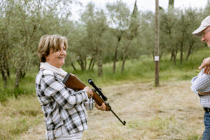 Senior woman at rifle target shooting, Florence, Italy