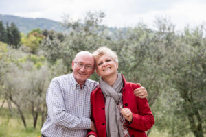 Portrait of senior couple, olive trees in background, Florence, Italy
