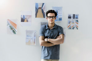 Portrait of young male architect standing in front of whiteboard with design ideas.
