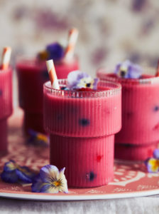 Close up of three glasses of pink smoothie decorated with pansy petals.
