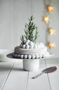 Close up of richly decorated Halloween cake with white icing and rosemary sprigs.