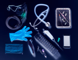 Potential way out of lockdown stage. Medical equipment on a black background, oxygen mask, stethoscope, mobile phone with a contact tracing app, syringes for vaccine, blue gloves and digital thermometer.