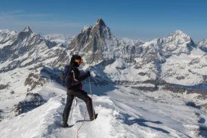 Schweiz, Wallis, Zermatt, Winterbesteigung, Bergsteiger auf dem Gipfel des Breithorn mit Dent d'Herens, Matterhorn und Dent Blanche im Hintergrund