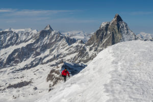Schweiz, Wallis, Zermatt, Winterbesteigung, Bergsteiger erreicht den Gipfel des Breithorn mit Dent d'Herens und Matterhorn im Hintergrund