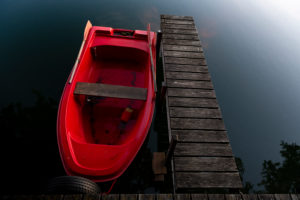 Red rowboat in the evening light on the jetty