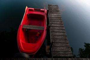 Rotes Ruderboot im Abendlicht am Steg