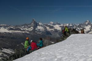Schweiz, Kanton Wallis, Saastal, Saas-Fee, Bergsteiger bei Gipfelrast am Allalinhorn mit Matterhorn, Dent d'Herens, Mont Blanc, Grand Combin, Dent Blanche