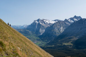 Switzerland, Canton Bern, Bernese Oberland, Grindelwald, two hikers on the descent from Tschuggen with a view of Titlis, Grosse Scheidegg, Wetterhorn, Mittelhorn, Bärglistock, Schreckhorn, Lauteraarhorn