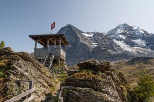 Switzerland, Canton Bern, Bernese Oberland, Grindelwald, Wengen, Kleine Scheidegg, lookout point with Swiss flag and view of Eiger north face, Mönch, Eiger glacier