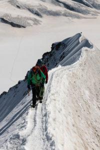 Schweiz, Kanton Bern, Berner Oberland, Bergsteiger am Gipfelgrat beim Aufstieg zum Mönch, im Hintergrund Ewigschneefäld