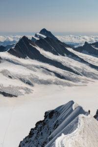 Switzerland, Canton Bern, Bernese Oberland, Canton Valais, mountaineers on the summit ridge when climbing to Mönch, in the background Ewigschneefäld, Fiescherhorn, Gross Fiescherhorn, Hinter Fiescherhorn, Finsteraarhorn, Klein Grünhorn