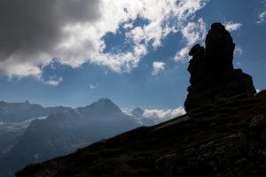 Switzerland, Canton Bern, Bernese Oberland, Grindelwald, First, rock formation at Hireleni with a view of Fiescherhorn, Hinter Fiescherhorn, Gross Fiescherhorn, Eiger north face, Jungfrau