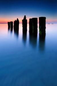 Sunset on the western beach, stone pyramids on old groyne, Darß, Baltic Sea, Mecklenburg-Vorpommern, Germany