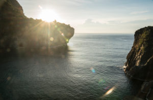 Bay with high rocks at sunrise and sunrays, sea, morning mood, untouched day