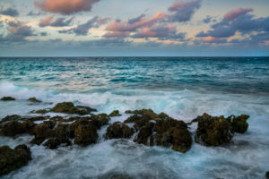 turquoise coloured sea with rock in the foreground and pink coloured clouds, at the blue hour, Malecon in Havana, Cuba
