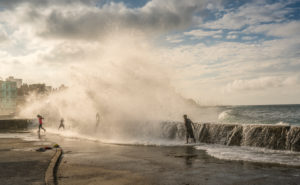 Gigantic wave hitting Malecon Havana, playing children, splashing surf, drops of water, Cuba