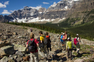 Hiking group in the scree field, Rocky Mountains, snowy mountains in the background, Canada