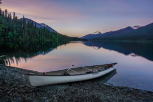 A white canoe lying at the lake, evening mood, with dreamlike mountain landscape