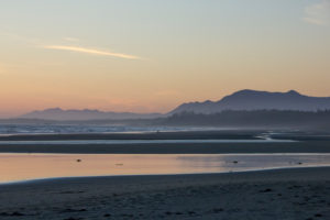Tofino, sea and beach in evening mood, mountains in the background, Canada