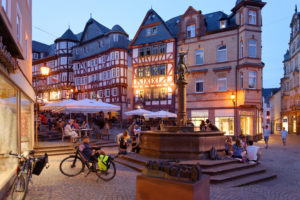Fountain at the market square with half-timbered houses in the evening light, Marburg, Hesse, Germany