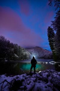 Abendstimmung und erster Schnee am Schlossweiher an der Hohenburg in Lenggries, Mann steht am See in der Abenddämmerung mit Stirnlampe