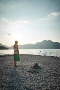 Frau bei Sonnenuntergang im Gegenlicht im Sommer am Walchensee, Bayern