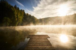 Spätsommerliche Morgenstimmung mit tiefliegendem Frühnebel über dem Waldweiher in Dietramszell, Bayern