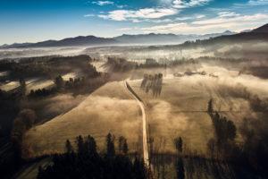 Drohnenaufnahme in der Morgenstimmung mit tiefliegendem Frühnebel über Wackersberg in Oberbayern im Gegenlicht