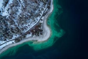 Drohnenaufnahme vom Walchensee in Bayern im November, Morgenstimmung, spiegelglattes Wasser und erster Schnee auf den Bäumen