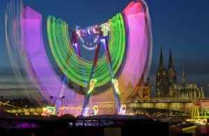 Germany, North Rhine-Westphalia, Cologne, funfair on the Deutz shore at night, view at the Cologne Cathedral,