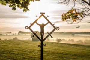 wayside cross in the morning light near Balterazhofen, Leutkirch, Baden-Wuerttemberg, Germany,
