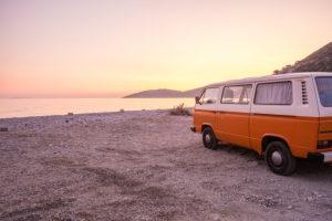 "An orange and white VW Bus ""Bulli"" stands at sunset on the beach of the Ionian Sea near Saranda (Sarandë), Albania."