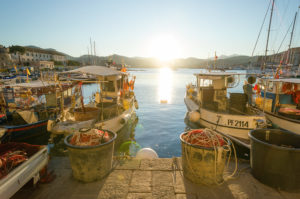 Fishing boats lie in the evening sun in the old port of Portoferraio, Elba, Toscana, Italy.