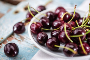 Cherries (Prunus) lie on a small porcelain plate on an old wooden table. Germany.