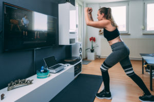 Europe, Germany, Rosenheim, Young Female is doing Sports Workout at Home, Livingroom
