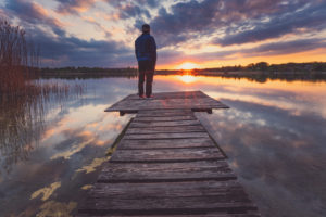 Europe, Germany, Bavaria, Breitbrunn, Chiemsee, Chiemgau, Chiemsee Lake, Man standing on jetty and looking into sunset,