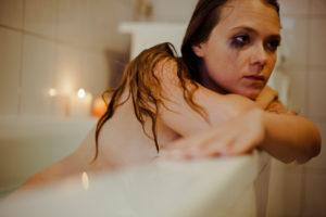 Woman in bathtub is thinking, sad feeling,