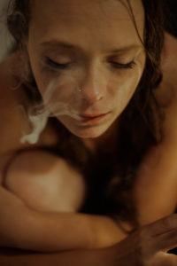 Sad Woman in bathtub is smoking a cigarette because she has bad mood,