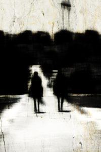 Die Silhouetten von zwei Reitern auf einem schmalen Weg,