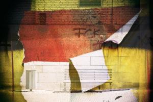 Abstrakte Montage einer Parkbank vor einer mit politischen Slogans bekritzelten Wand mit abgerissenen Papierfetzen,
