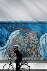 Streetart photography of a cyclist in front of a painting of the East Side Gallery,
