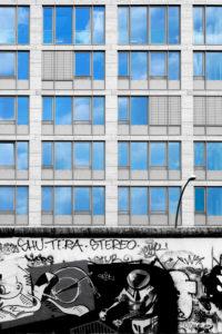 Ein Stück der Berliner Mauer an der East Side Gallery mit einem Kosmonauten und einem modernen Gebäude im Hintergrund,