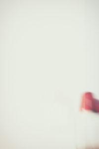 Eine verwackelte rote Warnleuchte mit Lautsprecher wirft Schatten an einer weißen Wand,
