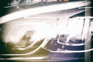 Nahaufnahme des Frontlichtes eines Kraftfahrzeuges mit Neonscheinwerfern.