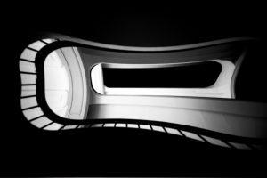 Die Untersicht auf einen Treppenaufgang mit einer Wendeltreppe und Geländer