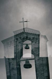 Der Glockenturm einer alten Kirche mit einer freihängenden Glocke.