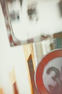 Die abstrakte Doppelbelichtung einer unübersichtlichen Kreuzungsecke mit einem Verkehrsspiegel und einer Geschwindigkeitsbegrenzung.