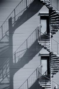 Eine Wendeltreppe, Feuerleiter, an der Seitenfassade eines Industriegebäudes.